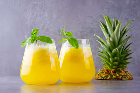 Pineapple juice on a gray background. Juice for detox in the glass. Pineapple smoothie with fresh pineapple. Healthy summer drink with mint