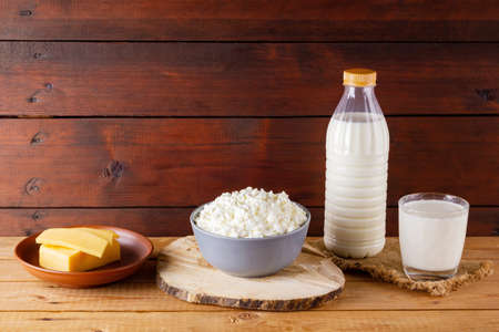 Dairy products on wooden boards. Milk, hard cheese and cottage cheese on burlap. Rustic style. Copy space