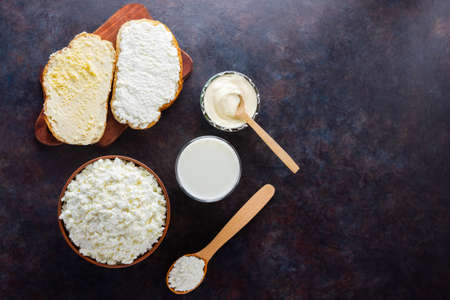 Various dairy products. Milk, cottage cheese and sour cream on a dark background. Bread with cream cheese on a black background. Top view
