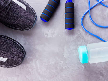 Fitness concept with sneakers, jump rope and bottle of water. Sports equipment on a gray background. Healthy lifestyle concept. Copy space. Top view