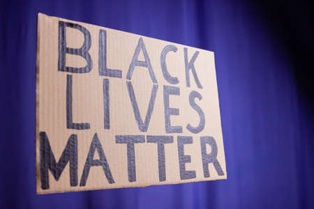 BLACK LIVES MATTER on a blue blurred background. No racism concept. Cardboard banner with a text