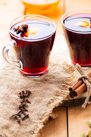 Mulled wine on a wooden background. Autumn mulled wine and spices on burlap. Christmas hot drink in rustic style