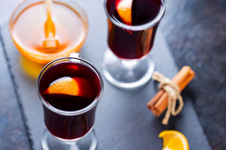 Mulled wine on a slate board. Two glasses of hot mulled wine and ingredients. Christmas hot drink with wine and honey