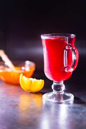Christmas mulled wine on a dark background. Glass of mulled wine glows in the backlight. Traditional hot drink at Christmas time Stock fotó