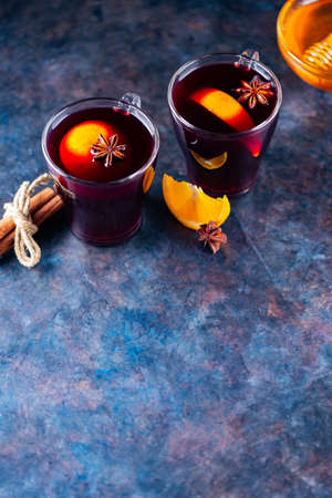 Mulled wine on a dark background. Two cups of autumn mulled wine and ingredients. Christmas hot drink with wine and honey