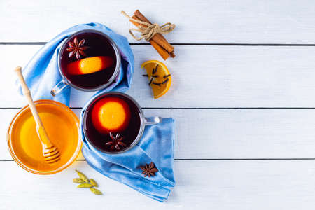 Mulled wine on white boards. Two cups of autumn mulled wine on wooden background. Christmas hot drink. Copy space. Top view