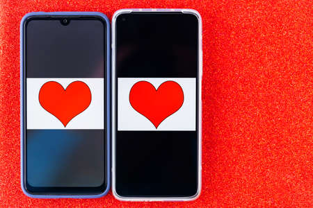 Online dating concept. Red hearts on the two smartphones screens. Valentine's Day concept on a red glitter background. Copy space. Top view