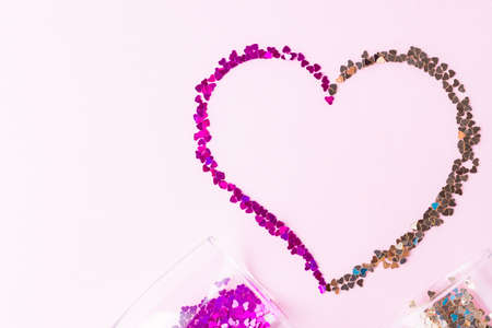Heart shape made of multicolored glitter. Two champagne glasses with splash of heart shaped confetti over pink background. Valentine's Day concept. Flat lay Reklamní fotografie