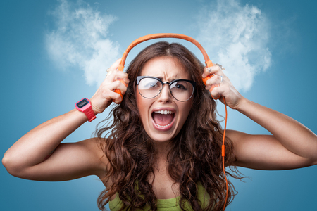 attitude girls: Angry nervous girl in headphones listening to music and screaming loud blowing white smoke coming out of ears. Closeup portrait girl on blue background. Negative emotion facial expression feeling