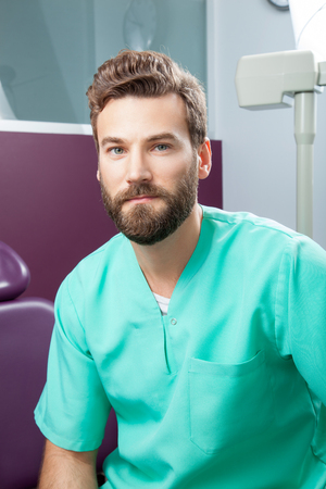 proffesional occupation: Portrait of serious young handsome attractive male doctor with beard in green costume sitting in dental clinic. Face expressions, emotion, healthcare, medicine. Stock Photo