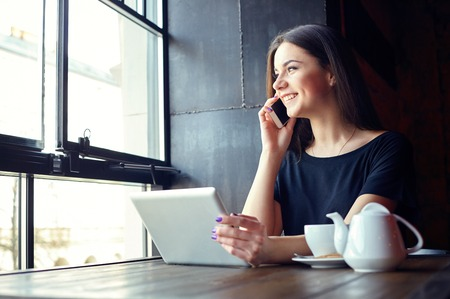 Giovane ragazza attraente parlando a telefono cellulare e smilling, mentre seduto da solo nel negozio di caffè durante il tempo libero e di lavoro sul computer tablet. Felice femmina che ha resto in caffè. Stile di vita, caffè