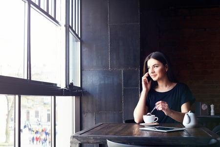 smilling: Young attractive girl talking on mobile phone and smilling while sitting alone in coffee shop during free time. happy female having rest in cafe. Lifestyle, coffee Stock Photo