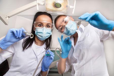 Femme médecin dentiste et son assistant dans des masques et des uniformes blancs tenant dans leurs mains miroir dentaire, sonde et d'autres équipements, regardant la caméra et souriant