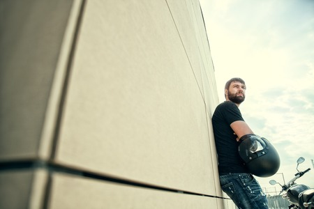 avenger: Portrait of biker men with beard in black shirt standing near a modern wall, holding helmet in his hands and looking away on sunset