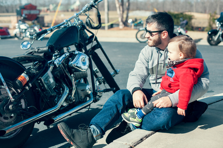 Handsome young father and cute little toddler son sitting on the ground and looking on black motorcycle stands near them on summer day outdoor. Lifestyle, vacation, happiness, joy concept Zdjęcie Seryjne