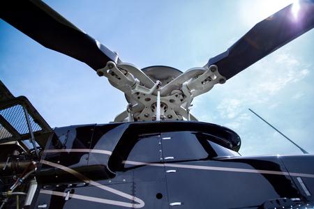 reportero: Cerca de un tornillo de negro con rayas grises helicóptero Bell 407 se coloca en campo de hierba verde en el fondo del cielo azul.
