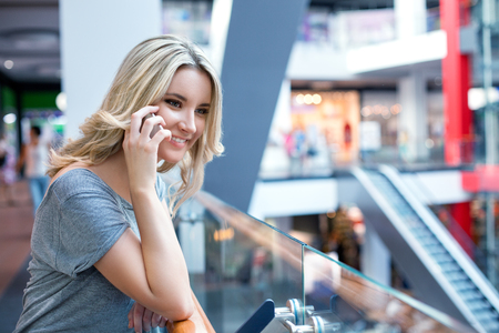 beautifull: Young happy hipster blonde girl with beautifull smile speaking with her friend by mobile phone while shopping in modern mall