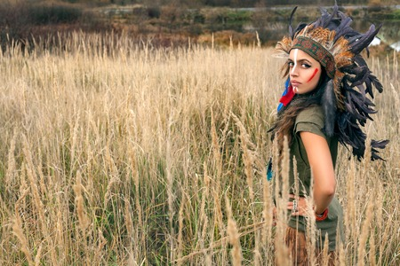 Beautiful girl model dressed in native American Indian clothes, with paint face camouflage and headdress with black,red and blue feathers and fur,looking serious on camera in summer field outdoors.