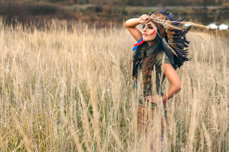 female shaman: Beautiful girl model dressed in native American Indian clothes, with paint face camouflage and headdress with black feathers and fur,looking at the summer field with hand on forehead.