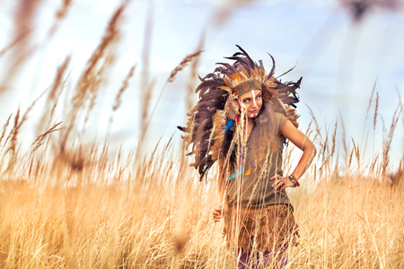 Beautiful girl model smilling with white teeth, dressed in native American Indian clothes, with paint face camouflage and headdress with black feathers and fur,looking at the summer field.