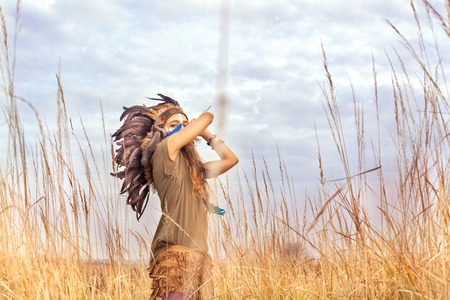 infatuation: Beautiful girl model dressed in native American Indian clothes, with face covered by a hand and headdress with black feathers and fur,looking at the camera in summer field.