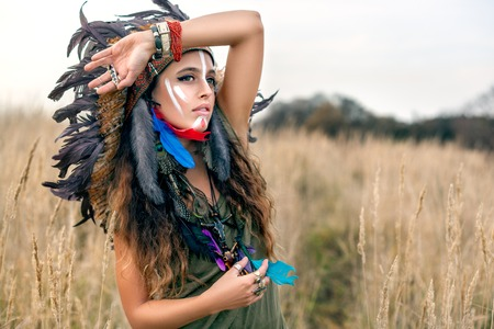 Beautiful girl model dressed in native American Indian clothes, with paint face camouflage and headdress with black feathers and fur,looking at the summer field with hand on forehead.