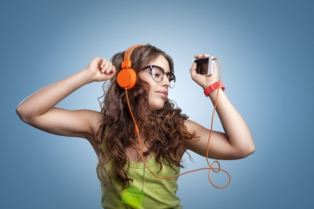 feelings and emotions: Beautiful girl with long curly hair in headphones and glasses with closed eyes listening to music and dancing. Portrait girl on blue background. Human facial expressions, emotions, feelings. Stock Photo