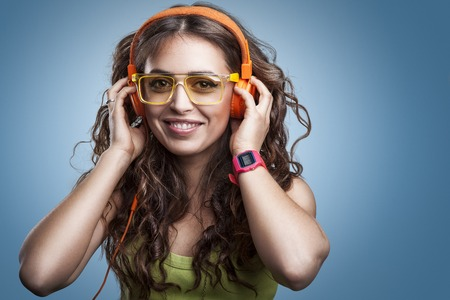 timepiece: Happy girl in headphones and glasses listening to music, enjoying and smiling.Closeup portrait female on blue background. Positive human emotion facial expression feeling
