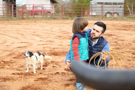 Father training small toddler boy son making loope and throwing lasso to bull in the ranch. Roping simulator. Red clay background, countryside. Family, relationship, free time