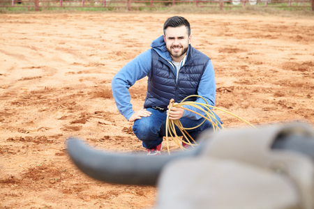 Handsome man with a beard training throwing lasso to a bull in the ranch. Roping simulator. Red clay background, countryside. Stock Photo
