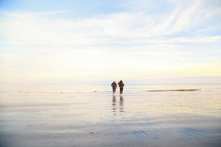 Couple standing on wet sand on beach and looking away. Man and woman relaxing on the sea ocean on sunset. Back view. Peaceful scene, calming waves, pastel cloudy sky, east coast. Happy time together. Stock Photo