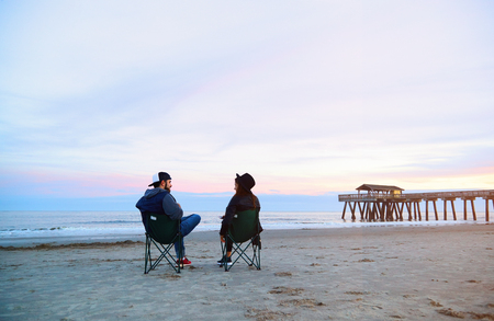 Couple sitting in deck chairs at beautiful sunset beach. Smiling man and woman in hats and casual clothes relaxing near ocean pier jetty. Calming waves, pastel cloudy sky, coast, wet sand