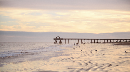 Ocean pier jetty at spectacular sunset. People walking on beach. Peaceful scene, calming waves, pastel cloudy sky, coast. Soft light Stock Photo