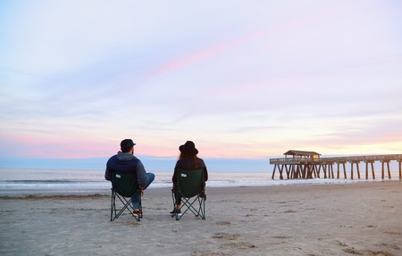 Couple sitting in deck chairs at beautiful sunset beach. Man and woman in hats and casual clothes relaxing near ocean pier jetty. Peaceful scene, calming waves, pastel cloudy sky, coast, wet sand.