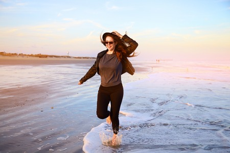 Smiling girl in hat running on beach on ocean coast. Female having fun in sea waves. Happy woman with long hair in leather jacket walking on wet sand and splashing water on sunset. Windy weather.