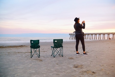 Woman in hat holding cell phone and making photo. Girl standing on beach with smartphone in hand. Female in black clothes using mobile phone near ocean pier jetty. Deck chairs standing on wet sand.