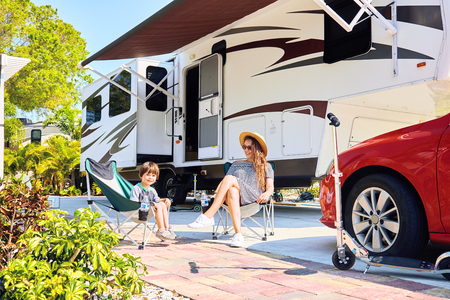 Mother And Son Sitting Near Camping Trailer,smiling.Woman And Kid Relaxing  On Chairs
