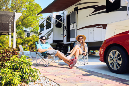 Young couple sits near camping trailer,smiling.Woman and men in casual clothes relaxing on chairs near car and palms.Family spending time together on vacation near sea or ocean in modern rv park