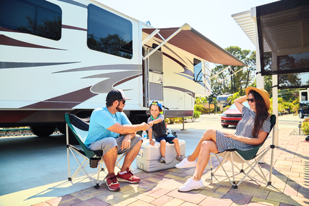 Mother, father and son sitting near camping trailer,smiling.Woman, men, kid relaxing on chairs near car and palms.Family spending time together on vacation near sea or ocean in modern rv park