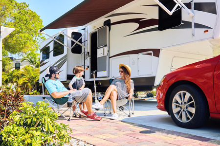 Mother, father and son sitting near camping trailer, smiling.Woman, men, kid relaxing on chairs near car and palms.Family spending time together on vacation near sea or ocean in modern rv park Stockfoto