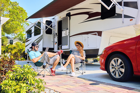 Young couple sits near camping trailer,smiling.Men uses electronic device, woman relax on chair near red car and green palms.Family spending time together on vacation in rv park