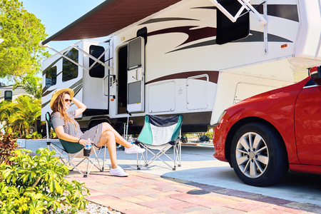 Young woman sits near camping trailer. Woman in casual clothes and hat relaxing on chair near red car and green palms. Family spending time together on vacation near sea or ocean in modern rv park