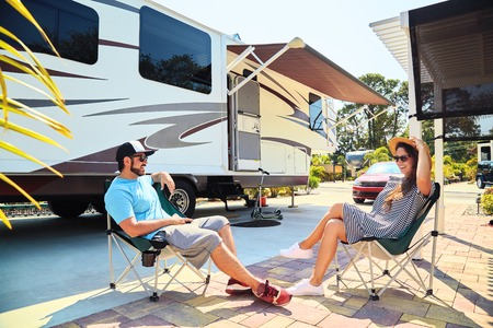 campervan: Young couple sits near camping trailer,smiling.Men talks on mobile phone and uses electronic device, woman relax on chair near car and palms.Family spending time together on vacation in rv park