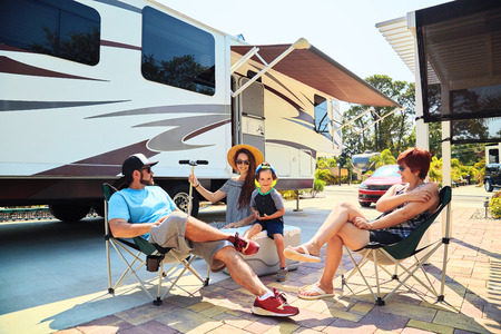Mother,father,son and grandmother sitting near camping trailer,smiling.Woman,men,kid relaxing on chairs near car.Family spending time together on vacation near sea or ocean in modern rv park Banque d'images