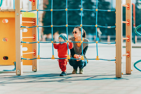 rope ladder: Mother and son on the Playground, walk around the childrens constructions, the boy stands and holds onto the rope ladder, the mother supports the child. Stock Photo
