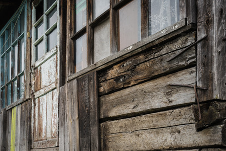 home destruction: Old Windows and cracked wooden wall, rustic home.
