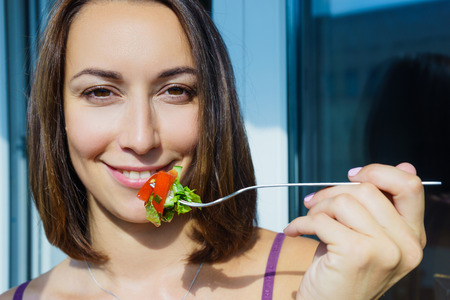 fresh leaf: A girl holding a fork with vegetables, smiling young girl, sunny day, with fresh vegetables, tomatoes and cucumbers, leaf lettuce. Useful food, vegetarian salad
