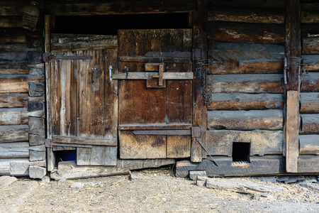 enclosure: Rustic wooden house, doors and shutters, kennel for the dog, logs and planks, beams, locking door, dust, dirt, hay. The stable, enclosure for livestock Stock Photo
