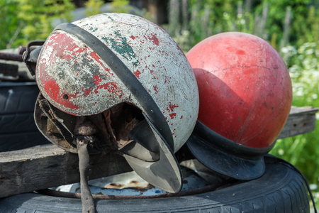 Old shabby motorcycle helmets. Obsolete helmets cracks, belts, mud, red and white. The bursting of the coating Stock Photo
