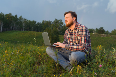 Man sitting on the grass with a laptop on his knees and looking thoughtfully into the distance. The concept of work in the countryside. A bearded man in a plaid shirt. Rainy evening, the setting sun. The hill and the forest landscape. Recreation and Leisu